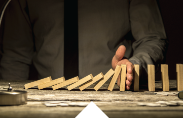 A Man using his hand to prevent a line of standing wooden blocks from toppling over onto other wooden blocks